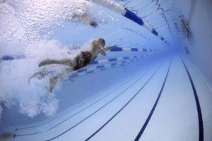 Homme plongeant dans la piscine